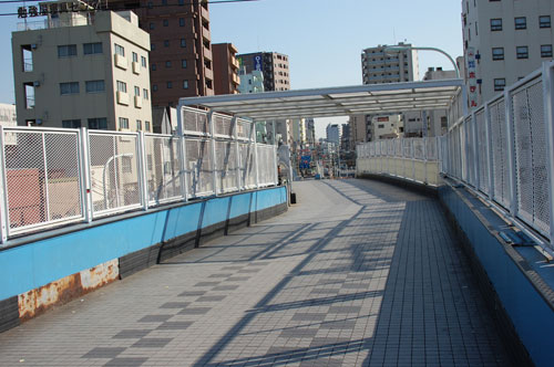 目の前にある陸橋を渡って頂き逆口に下りて下さい。